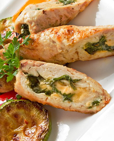 Stuffed chicken fillet with spinach and cheese, served with grilled vegetables and fresh parsley on white plate photo