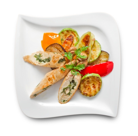 Overhead shot of stuffed turkey breast, grilled and sliced with grilled vegetable. See more food files photo