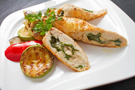 Stuffed turkey fillet with spinach and cheese, served with grilled vegetables and fresh parsley on white plate photo