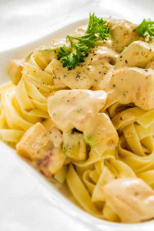 alfredo: Close-up shot of chicken alfredo fettuccine with fresh parsley and wisible white meat chunks in rich sauce Stock Photo