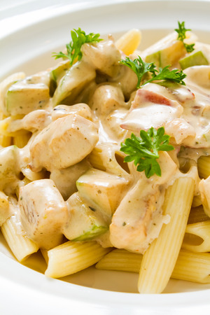 Close-up studio shot of Penne Chicken Alfredo in rich creamy sauce. Ideal for blogs and recipe books