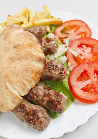 Freshly grilled kebab cevapi with tomato photo