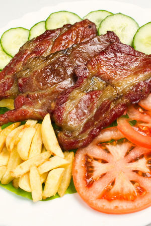 Beautifully grilled and slightly smoked pork cuts served o white plate with cucumbers, tomato and fries photo