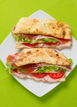 woodfire: Homemade sandwich with ham, cheese, tomato and lettuce in woodfire oven bread bun on green