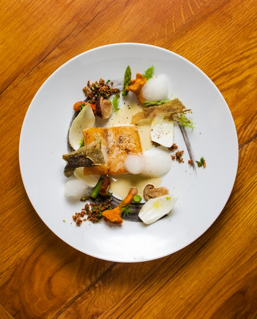 plating: Modern plating of sea bass with assorted mushrooms, asparagus, nuts and dill.  Stock Photo