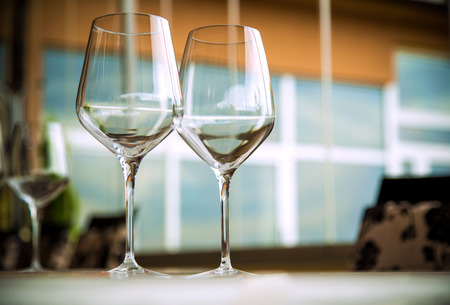 Natural light or daylight shot of modern restaurant table set for a lunch. Shallow focus on wine glass