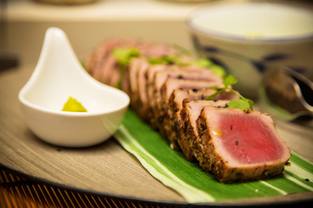 black dish: Seared tuna steak called Sashimi traditional Japanese dish with wasabi sauceon side Stock Photo
