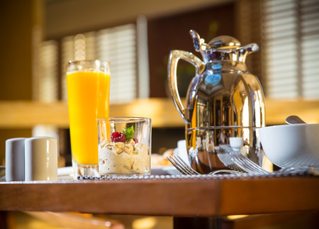 Morning scene of hotel or residential breakfast with coffee cup in focus and jug