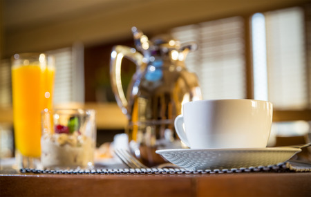 light breakfast: Morning scene of hotel or residental breakfast with coffee cup in focus and jug, glass of orange and muesli in blurred background. See more catering industry shots