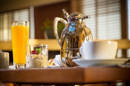 Morning scene of hotel or residental breakfast with coffee cup in focus and jug, glass of orange and muesli in blurred background. See more catering industry shots