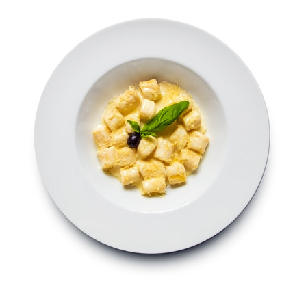 Restaurant shot of perfectly made gnocchi pasta with lots of shreded cheese and creamy sauce decorated with fresh basil and  black olive Stock Photo - 34733466