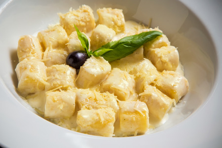 Restaurant shot of perfectly made gnocchi pasta with lots of shreded cheese and creamy sauce decorated with fresh basil and  black olive
