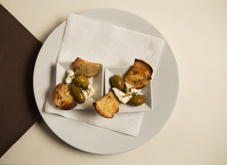 Restaurant shot of tiny bruschetti mezze style feta cheese and green olives. Finger food concept See more