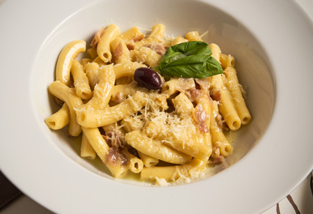 penne: Penne pasta Carbonara with ham in rich creamy sauce with olive and basil Stock Photo