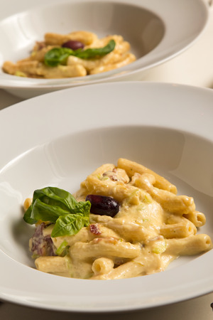 Penne pasta Carbonara with ham in rich creamy sauce with olive and basil Stock Photo