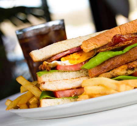 Very crusty club sandwich with chicken bacon fried egg tomato letuce toasted bread fries and soft drink Stock Photo