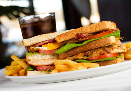 Very crusty club sandwich with chicken bacon fried egg tomato letuce toasted bread fries and soft drink Stock Photo - 70640552