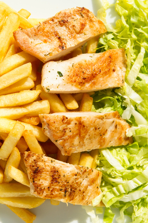 Grilled chicken fillet with fries and lettuce on a sunny day
