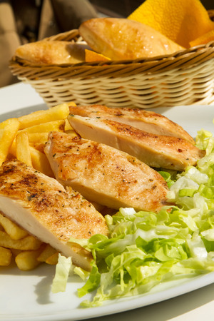 Grilled chicken fillet with fries and lettuce on a sunny day Stock Photo - 70820791