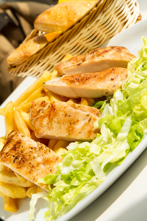 Grilled chicken fillet with fries and lettuce on a sunny day Stock Photo - 70818710