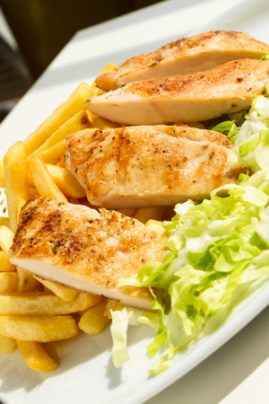 Grilled chicken fillet with fries and lettuce on a sunny day Stock Photo - 70818709