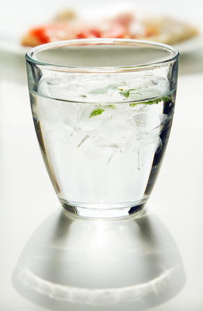 Glass of water with ice cubes and mint in backlight scene with shadow