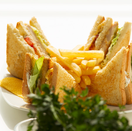 Club Sandwich with fries on sunshine, arranged and splited