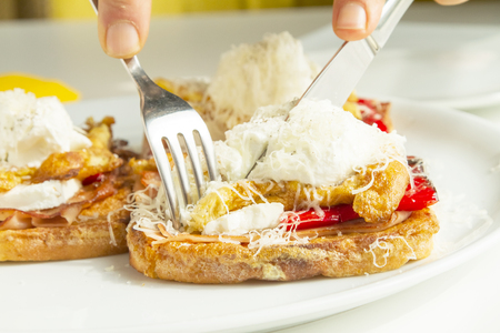 French toast topped with ham, grilled pepper, scrambled eggs and a ball of cream cheese Stock Photo