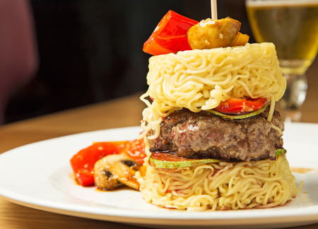 Grilled beef burger served in rice noodle stack with grilled vegetables and sesame seed Stock Photo