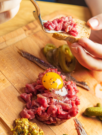 Using fork for placing Tartara steak on a bread see more Tartara or Tatar in gallery