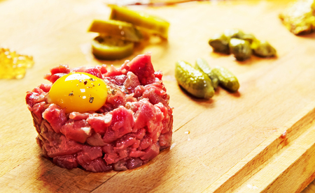 Beef Tartare served with caviar, crushed mustard seeds sauce, picked jalapeno peppers and marinated fish