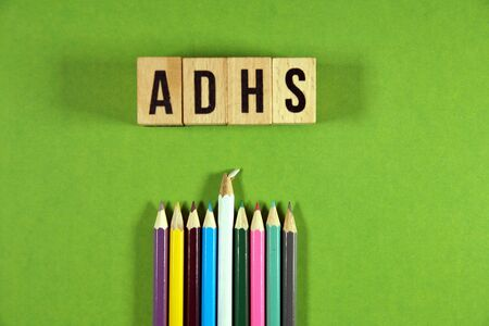 The german word ADHD attention deficit hyperactivity syndrome on wooden cubes with multicolored pencils on green background. ADHD concept Stock Photo