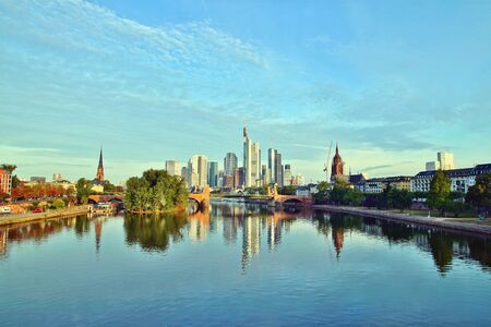 Frankfurts skyline reflecting on the river on sunrise. European city skyline and financial center of Frankfurt. Germany Skyscraper buildings on blue sky background. Business and finance concept