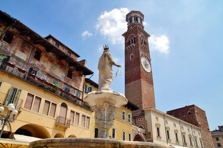 Back view of Fountain statue of Madonna and Lamberti tower with clocks on Heritage Square in Verona city, Italy. Torre dei Lamberti over blue sky, famous clock tower in Piazza delle Erbe 写真素材