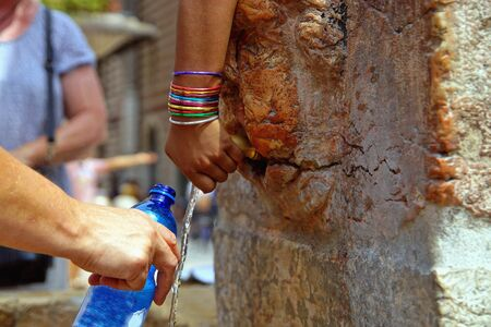 Closeup on childs hand with colored jewelry bracelets. Hand of thirsty tourist taking fresh cold water. Refilling small plastic bottles in the city of Verona. Cold healthy water into bottle. Italy 2019. Reklamní fotografie
