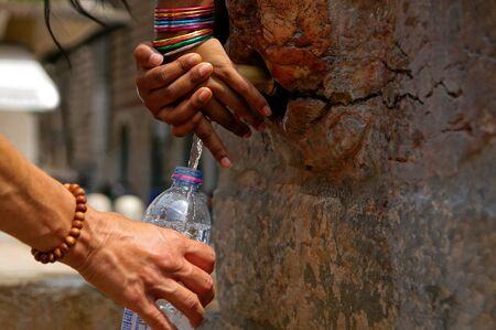 Fountain spout in Verona, July 2019. child with colored jewelry bracelets.Hand of thirsty tourist taking a fresh cold water. Italy for fresh drinking water.