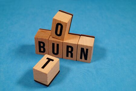 Burnout Word Written In Wooden Cube. Burn out, cube with letters. dice with text. concept of the destruction of shortcomings, fears, burnout at work, daily routine. medical or health care concept
