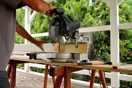 Carpenter using a circular saw to cut a wooden beam. Woodworking and carpentry production. Wooden beams spruce for outdoor construction, wood beams for carport. woodwork concept.mans hands is working