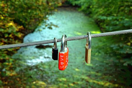 Locks of love in the shape of a heart on a pedestrian bridge, green water, river background. Padlocks, love locks lettered with love