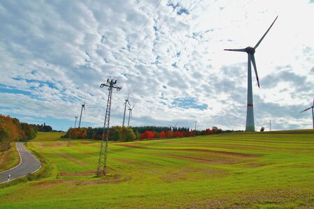 Wind turbines and high voltage tower against the sun, autumn landscape. high-tension pylons against cloudy sky. power line transmission tower in along the road. alternative energy, new natural scenery