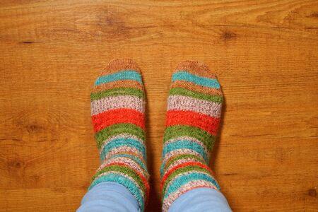 Woolen socks on wooden floor, Legs in knitted socks as a symbol of country life, winter cozy scene