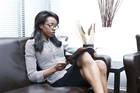 beautiful black women at home sitting reading a magazine Reklamní fotografie