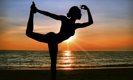 practicing yoga at sunrise on the beach Stock Photo