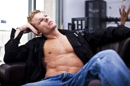 young muscular men sitting at home thinking photo