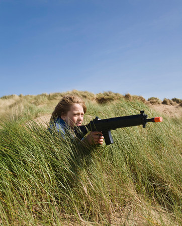 Boy in dunes with toy gun
