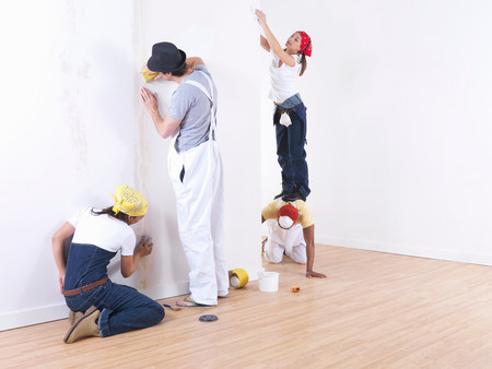 home decorating: Group of friends sanding wall. Stock Photo