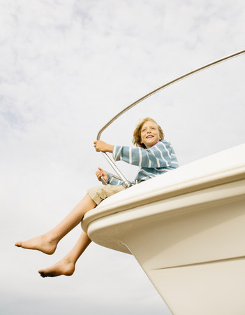 Boy on bow of yacht