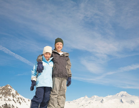 Boys together in snowy mountain scene Stock Photo