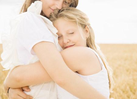 Girls hugging in wheat field Stock Photo