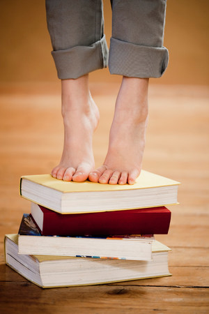 low spirited: young girl standing on books